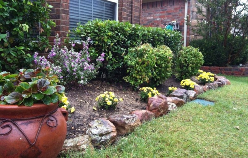 rock garden designs front yard with flower bed and green grass plus potted plants